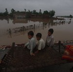 Some Pakistani children sharing the view from a makeshift bed after massive floods swept away their home. (Photo Credit:Shabbir Hussain Imam/IPS)
