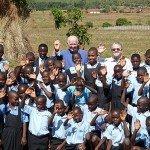 Estudiantes de quinto grado de Nuestra San Escuela primaria de Parroquia de Joseph Jesuit en Kasungu, Malawi visitan el área de la futura el colegio de secundarias Loyola. Foto de: LJSS