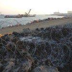 La emergente estructura del puerto en la distancia está rompiendo la roca natural y la tradición de la pesca por las mujeres de la comunidad. Foto de: P Walpole