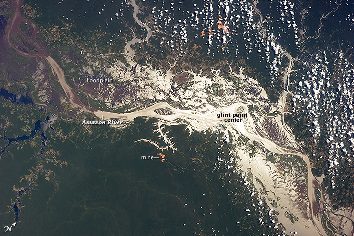 The Amazon River from 290 kilometers above the earth, taken 19 August 2014 by astronauts aboard the International Space Station, as it snakes through a floodplain more than 32 kilometers wide, with the sunglint from the water surface revealing the numerous lakes and side tributaries on the floodplain. Photo credit: earthobservatory.nasa.gov