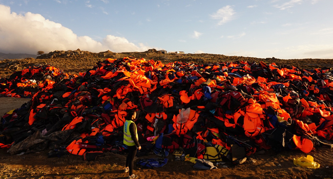 The life jacket graveyard piled in the hills of Lesbos, one of a series of photos by Ms Colleen Sinsky (http://jesuits.org/story?TN=PROJECT-20160229043205), an economics graduate from Santa Clara University, who cut short her Mediterranean vacation last December to help refugees and whose stories she shared and blogged. Photo credit: jesuits.org