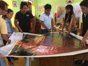 Funcionarios del gobierno local de Hernani, Samar Oriental, revisan un mapa de peligro de mareas de tempestad y las ubicaciones de las casas con el personal de investigación ESSC Dallay Annawi y Jericó Espada (más a la derecha)