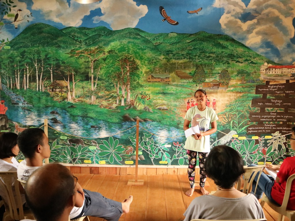 Ms Mercy Pakiwag, a Pulangiyen community member, shares her community's concerns and actions in the culture and ecology session of the Living Laudato Si' workshop recently held in Bendum, Mindanao, Philippines with around 30 Asia Pacific participants. The backdrop is a Pulangiyen community mural of their ancestral domain. Mercy joins the Vatican's international conference on the 3rd anniversary of Laudato Si' on 5 to 6 July. (Photo by A Ignacio/ESSC)