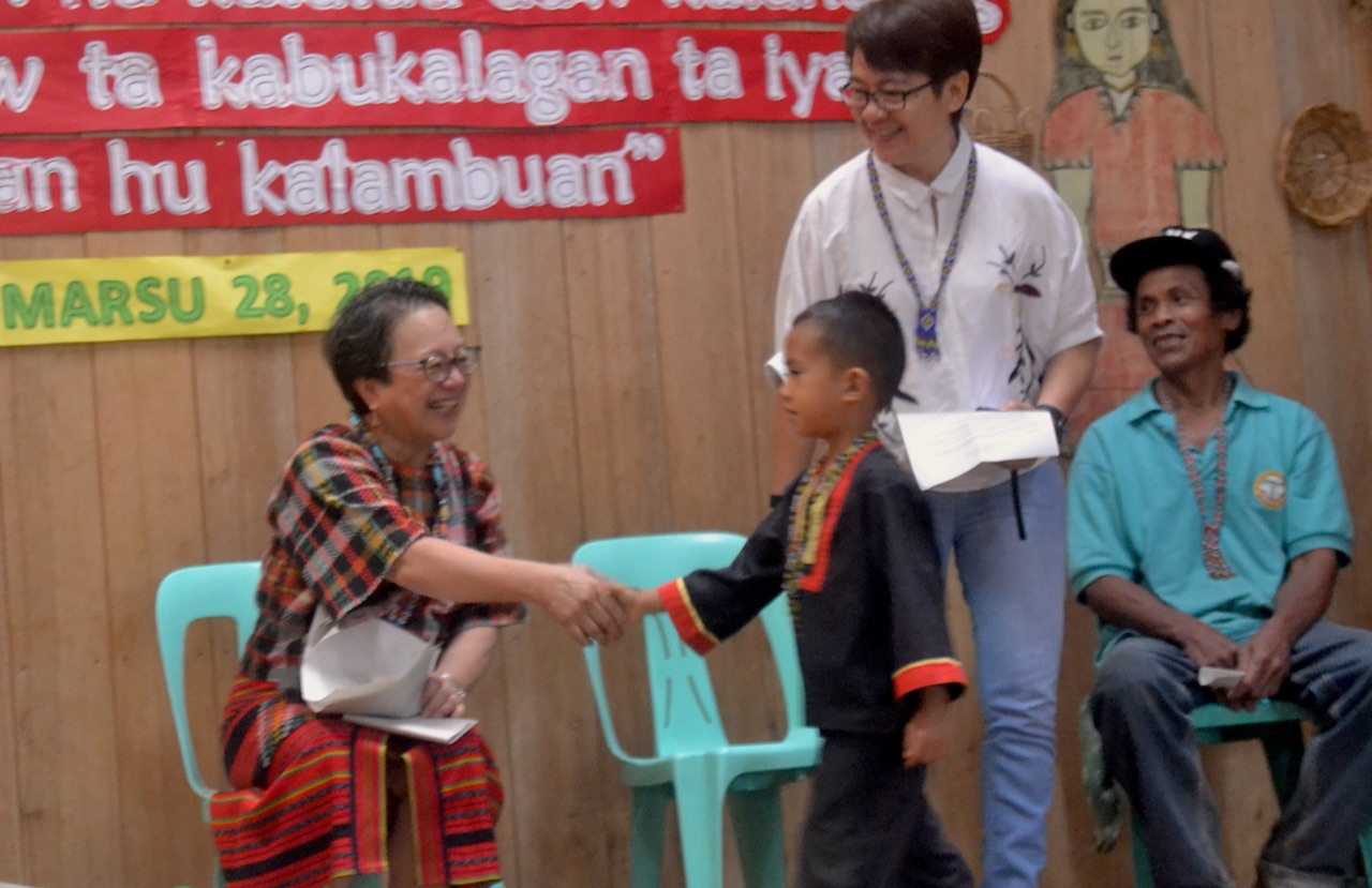 An APC Kinder student receives his congratulations from officials of the UN and Department of Education.